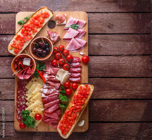 Fotografering Meat and cheese appetizer set for red wine on rustic background, flatlay, copy space