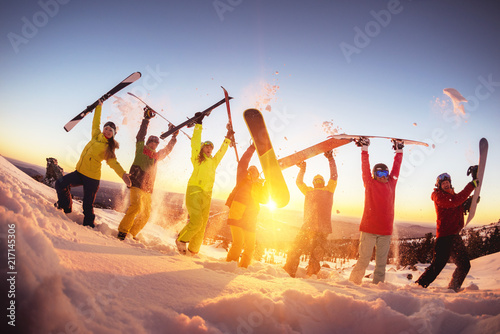 Valokuvatapetti Happy friends at ski resort having fun sunset