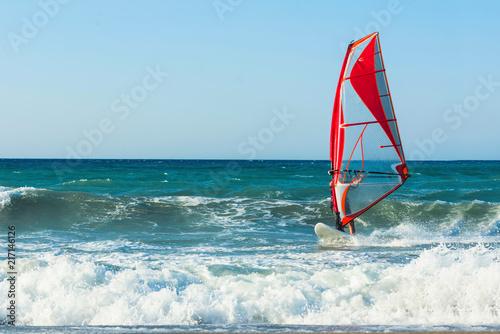 Windsurfers in the sea on Crete on sunset. Windsurfing in Heraklion