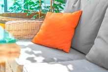 Orange Pillow On Gray Sofa With Floral Sunlight Background On Summer Terrace Or Cafe. Mockup For Advertising