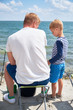 Father teaching his son fishing against view of sea and landscape