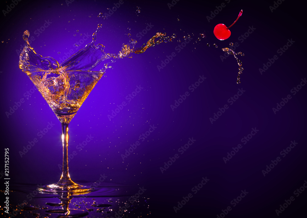 Fototapety, obrazy: red cherry splashing out of a martini glass on a purple background