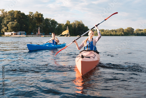 Keuken foto achterwand Ontspanning Beaming woman. Beaming blonde-haired woman wearing life vest holding paddles while kayaking