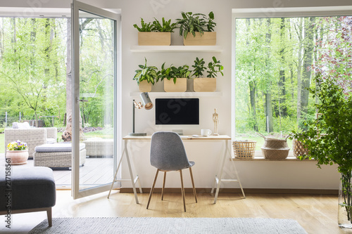 Obraz Inspirational workspace interior for a freelancer with computer on a wooden desk, white walls and the view of nature in the backyard outside - fototapety do salonu