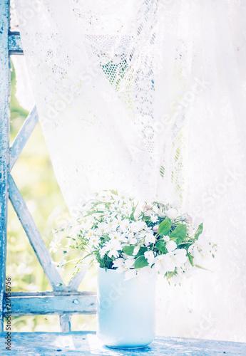 delikatne-biale-lesne-kwiety-w-niebieskiej-flizance-na-starym-oknie