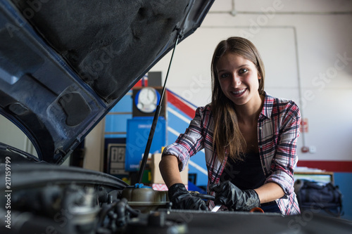 Young casual woman smiling at camera while fixing car engine and working in car service