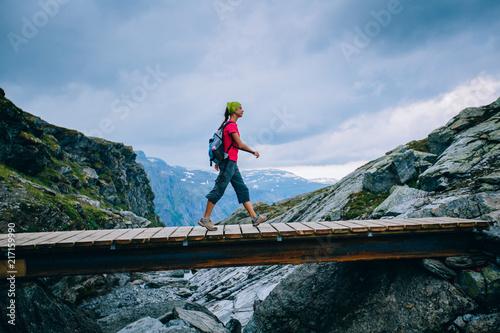 Fotografia Young sportive woman tourist hiker on rocky trail crossing a wooden bridge over Norway scandinavian landscape background