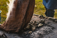 A Man Pulls A Burlap Sack Off Roasting Oysters