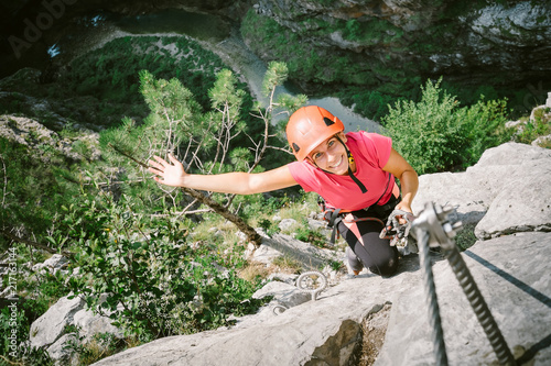 Fotomural Young happy woman who is climbing along a via ferrata