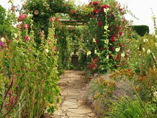 Path Through Flowers And A Pergola In An English Garden In Summer