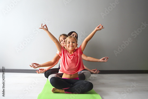 In de dag School de yoga Young woman having fun with kids doing yoga