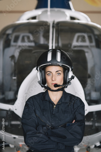 Portrait attractive woman helicopter pilot In the hangar