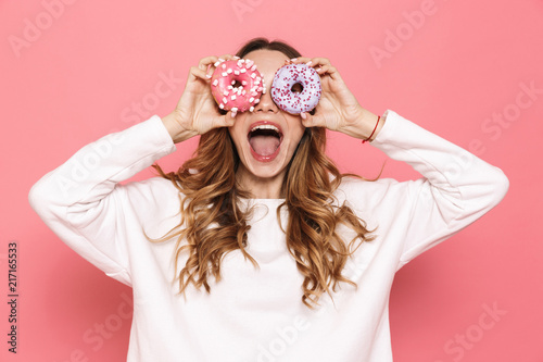 Photo  Portrait of a happy young woman showing donuts