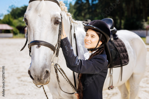 Poster Equitation Racing horse. White racing horse standing submissively near his female owner wearing dark helmet