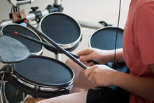 Unrecognized Boy In Pink T-shirt Practicing Electronic Drums With Black Drumsticks