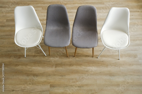 Group Therapy Counseling For Addicts U0026 Alcoholics Concept. Multiple Loft  Style Empty Chairs, White U0026 Gray, Standing In Row On Wood Textured Floor.