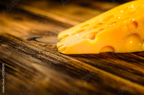 Piece of cheese on wooden table. Selective focus