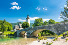 Bohinj Bridge And Church, Slovenia. Look To Old Historic Ancient Bridge And The Church Near The Bohinj Lake, In Triglav National Park. The Ribcev Laz Village. Sunny Sky With Clouds, Summer Weather