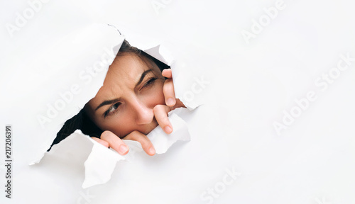 Fotografía  Portrait of a woman looking through the hole in white paper