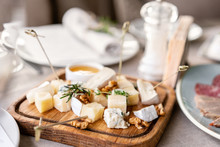 Cheese Plate. Delicious Cheese Mix With Walnuts, Honey On Wooden Table. Tasting Dish On A Wooden Plate. Food For Wine.