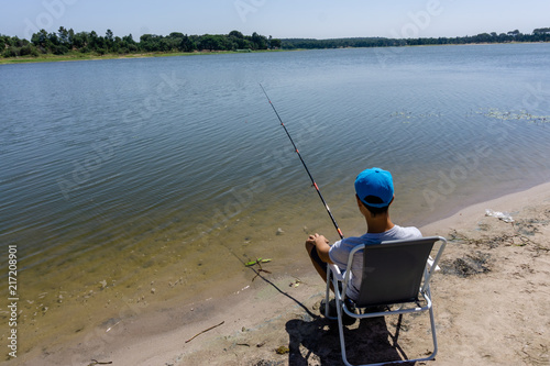Fotobehang Vissen boy teenager is fishing on the fishing rod in summer.