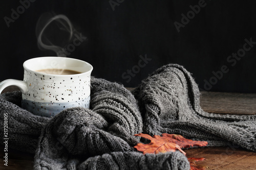 Fotografie, Obraz  Hot steaming cup of coffee with cream wrapped in a cozy grey scarf with fallen leaves for autumn