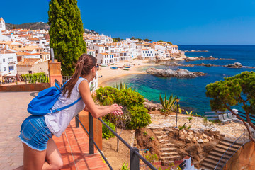 Tourist woman in Calella de Palafrugell, Catalonia, Spain near of Barcelona. Scenic fisherman village with nice sand beach and clear blue water in nice bay. Famous resort destination in Costa Brava