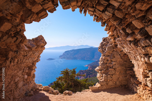 Sea skyview landscape photo from ruins of Monolithos castle on Rhodes island, Dodecanese, Greece. Panorama with green mountains and clear blue water. Famous tourist destination in South Europe