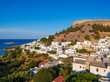 Aerial birds eye view drone photo of village Lindos, Rhodes island, Dodecanese, Greece. Sunset panorama with castle, Mediterranean sea coast. Famous tourist destination in South Europe.