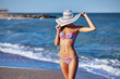 Sexy beautiful woman in color swimwear and hat at the sea coast. Exotic country travel and rest concept.