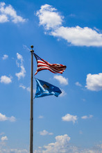 USA And Oklahoma Flags Flying Against A Very Blue Sky With Fluffy White Clouds On A Windy Day