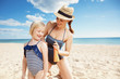 smiling mother and daughter on seashore applying sun cream