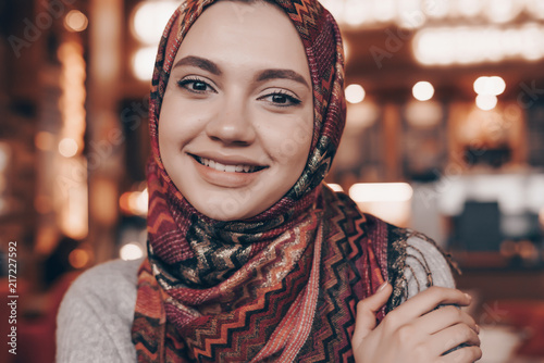 Photo beautiful an Arabian girl with a headscarf on her head posing in a cafe, looking