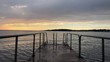 Still shot of a colorful sunset by the coast of sweden with closeup of a bathing platform in the foreground.