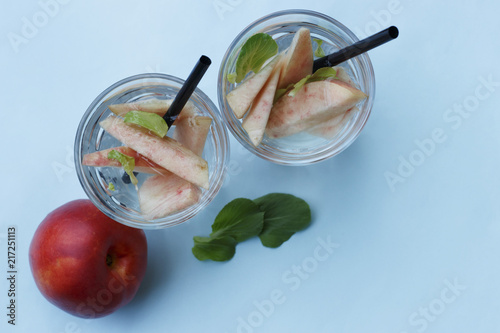 Fototapeta Two glasses with homemade iced tea with pieces of peaches. Summer refreshing drink, top view obraz na płótnie