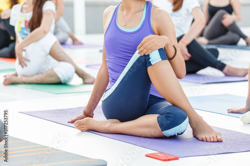 Fotobehang School de yoga Young sporty woman practicing yoga at class, doing stretching exercise. Close-up detail view of leg and hand