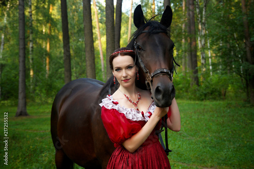 Beautiful young girl in retro dress posing near horse Canvas Print