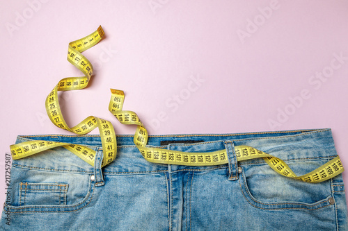 Cuadros en Lienzo Jeans and yellow measuring tape instead of belt on pink background