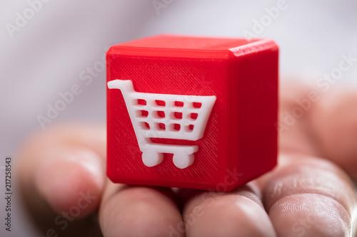 Fotografía  Person holding shopping cart cubic block