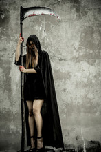 Asian Woman Dress Black As Grim Reaper Of Death And Holding Or Wielding A Large Scythe In Halloween Festival. Halloween Concept.