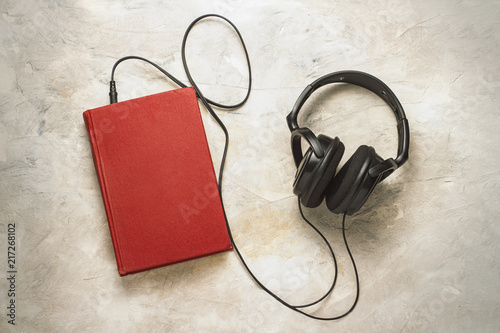 Valokuva  Book and headphones connected to it on a white stone background.
