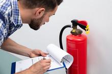 Man Checking Fire Extinguisher...
