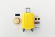 Flat lay yellow suitcase with traveler accessories on white bright background. travel concept. 3d rendering