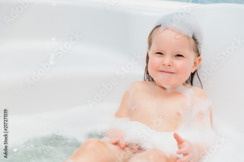 little girl have fun in the bath with soap on head #217271519