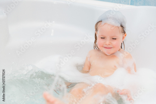 little girl have fun in the bath with soap on head #217271524