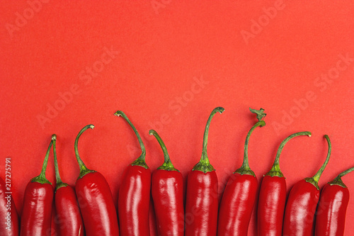 Chilli pepper on a red background with copy space.