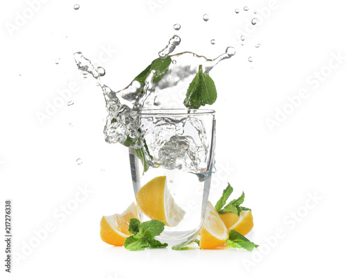 Poster Eclaboussures d eau Glass with splashing water and sliced citrus fruit on white background