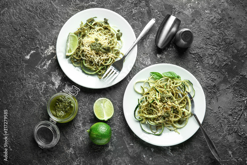 Plates of spaghetti with zucchini, pesto sauce and cheese on table Fototapeta