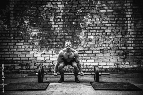 Foto  Muscular fitness man doing deadlift a barbell over his head in outdoor, street gym
