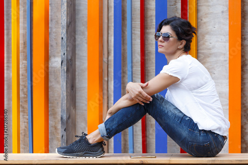Foto  A brunette woman in jeans and sunglasses sits on a wooden stage